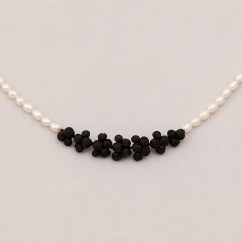 Black flowers between fresh water pearl necklace