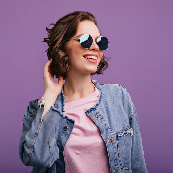 Smiling fashionable woman wearing sunglasses and a jean jacket.