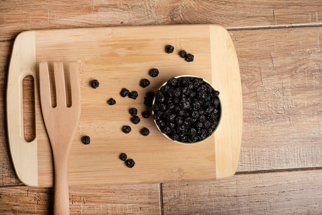 Bowl of dried blueberries on a wooden table