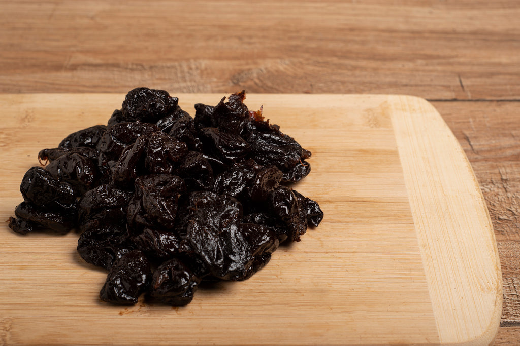 Pitted prunes on a wooden table