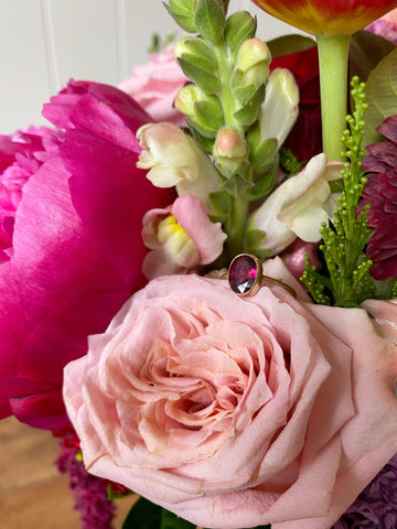 Garnet and gold ring atop a bunch of flowers
