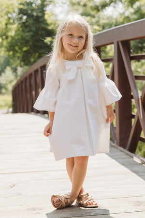 Blonde girl on a Bridge Wearing White Dress
