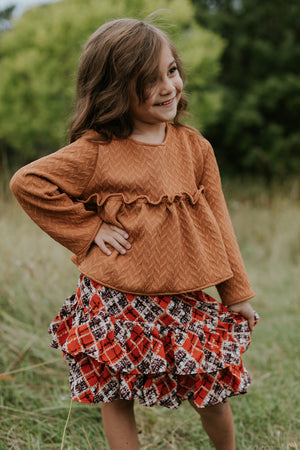Sassy girl wearing a top and a printed skirt