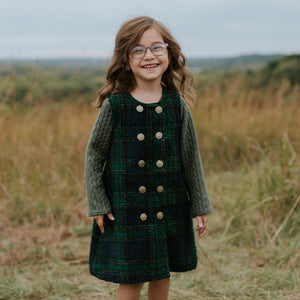 Girl with Glasses Smiling in a Plaid Outfit