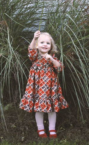 Little Girl Playing in Grass with a Plaid Dress on