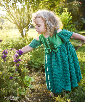 Curly Haired Girl Smelling Flowers in a Green Dress