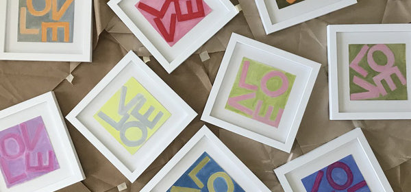 Framed paintings on paper with the word LOVE in different colors