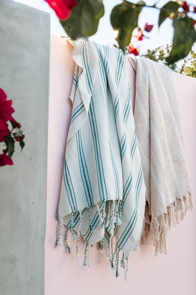 blush Turkish towel with cream stripes hanging with aqua striped towel