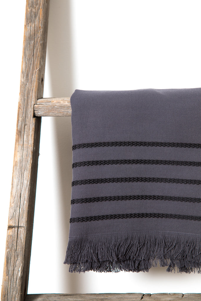 dark grey cotton hand towel with thin black stripes on the top edge and white fringes on the side