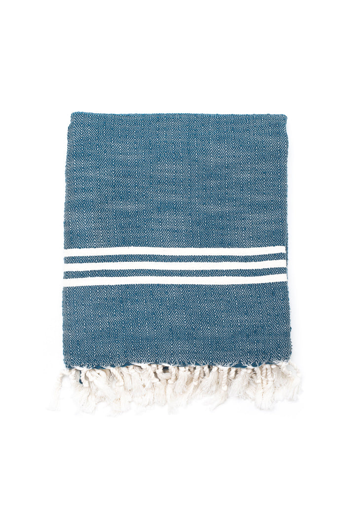 deep blue colored Turkish towel with 3 white stripes and white tassel fringes
