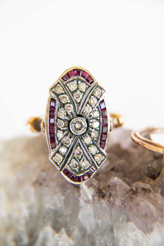 oval diamond ring with ruby along the edges and diamonds in the center