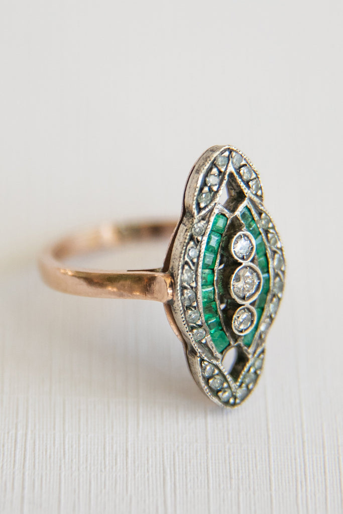 emerald and diamond ring with 3 little diamonds in the middle