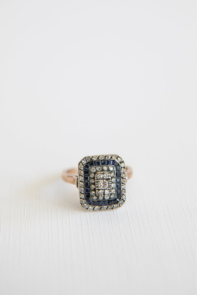 square shaped diamond ring with sapphire along the edges