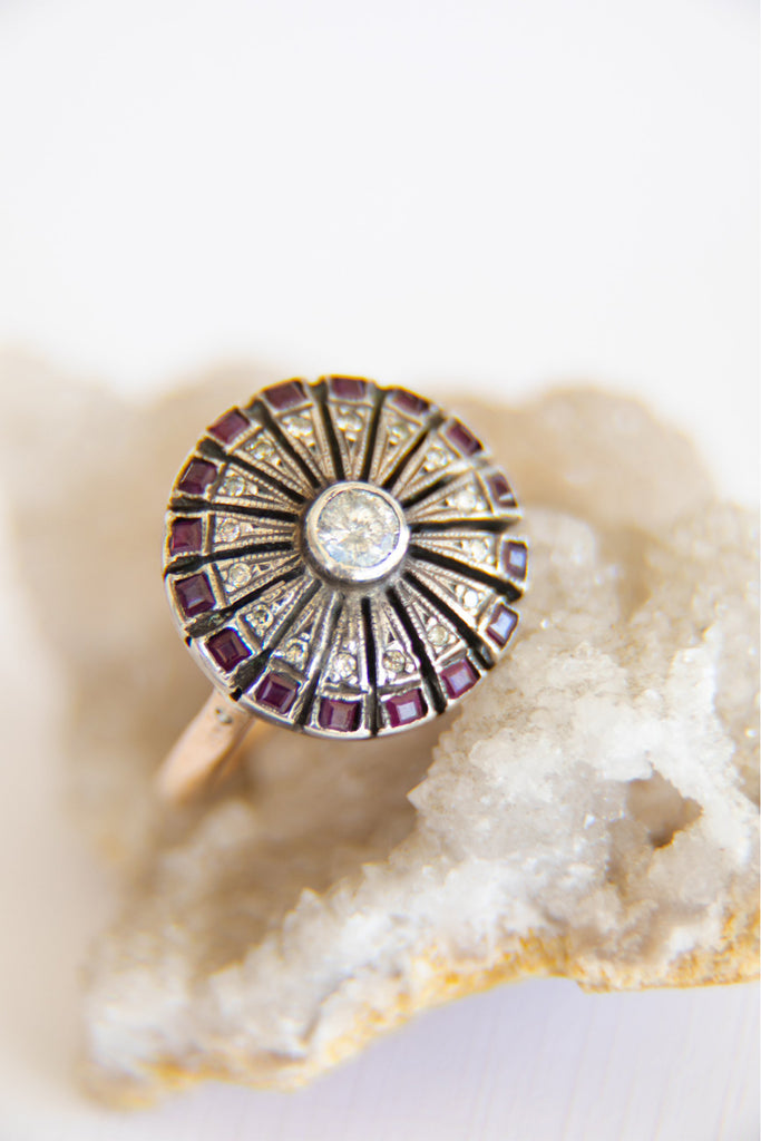 circular ring with rubies along the edges and a diamond in the middle