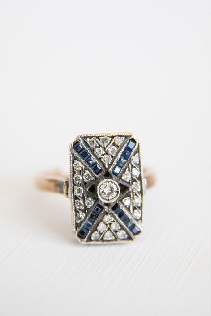 rectangular shaped ring with diamonds and sapphire crossed and a centered diamond in the middle