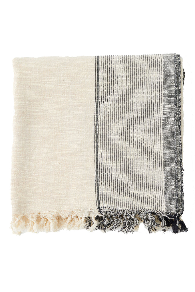throw blanket with thin grey stripes on the edge , and hand knotted tassels on the edge