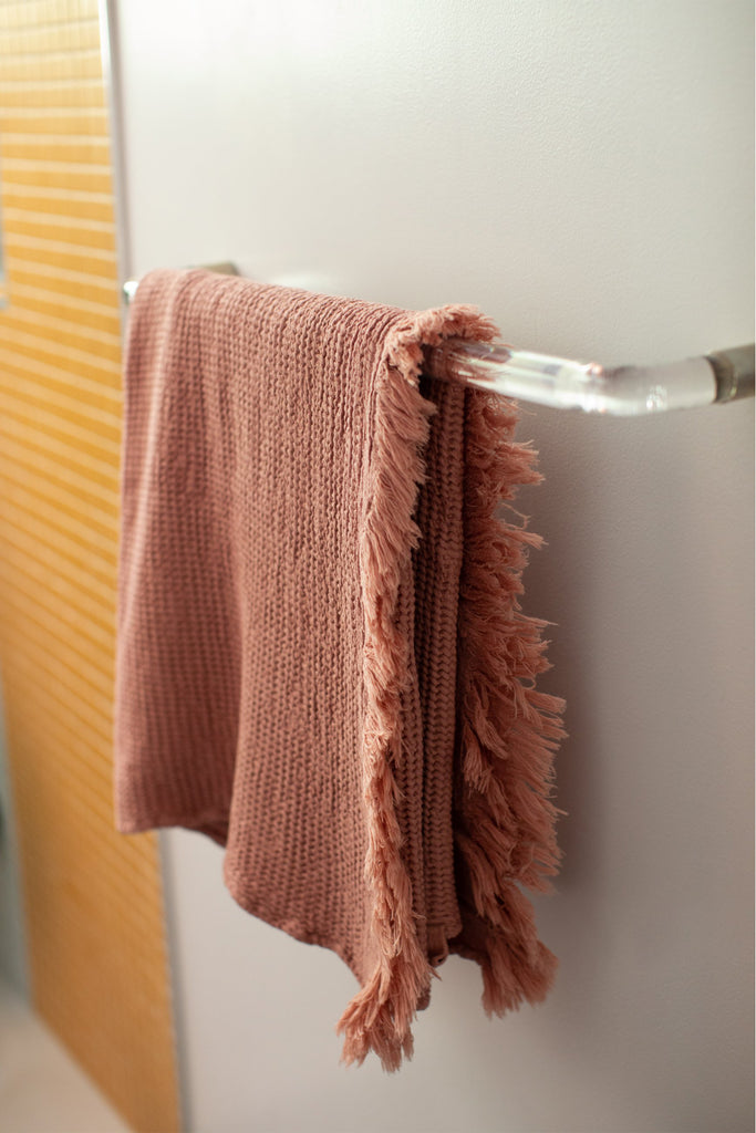 honey comb weaved hand towel in the color rose pink hanging in the restroom