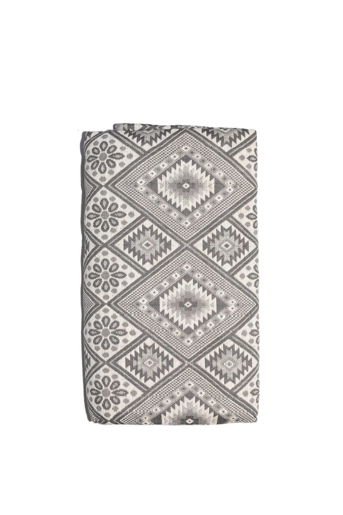 grey and cream bedspread with tile design including diamond shapes and flowers
