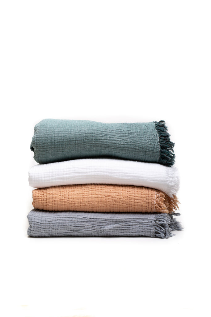 reversible double gauze soft blanket in forest green, white, peach, and grey.