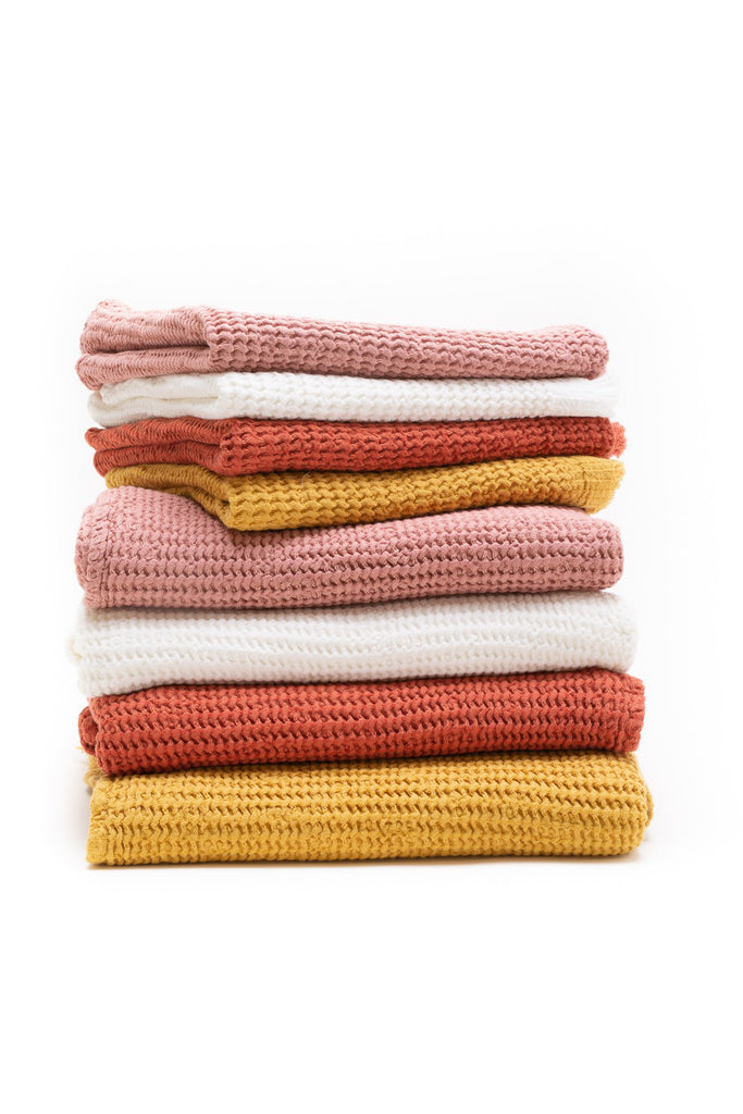 honey comb weaved hand towels in the color rose, white, brick, and mustard yellow