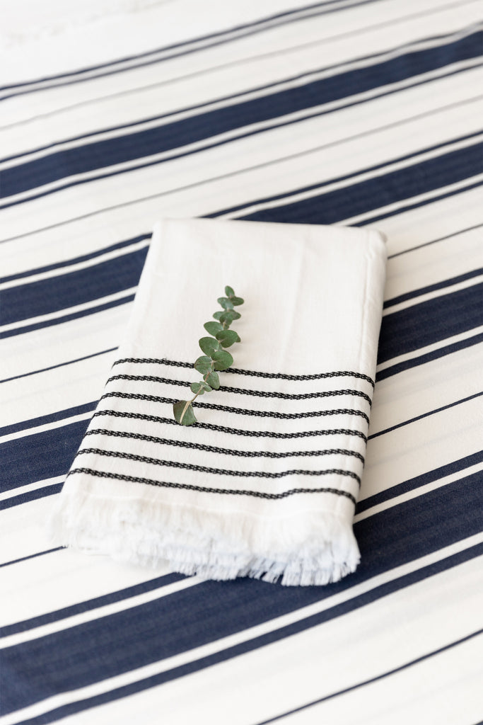 white hand towel with black mediterranean braids