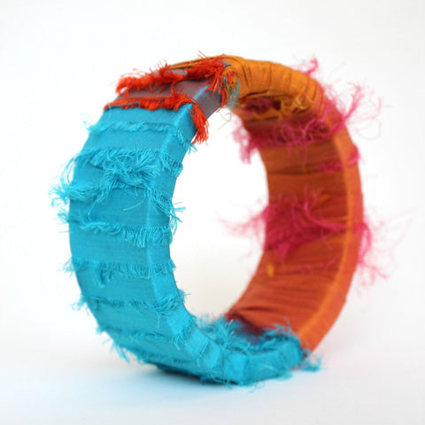 Bold bangle bracelet wrapped in turquoise and orange sari silk strips. An eco-friendly statement piece by worthygoods, handmade in Maine.