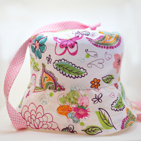 Newborn girl Trick Sun Hat, a reversible cotton sun hat in pink, white floral with gingham ties. Handmade in Maine by worthygoods. American made.