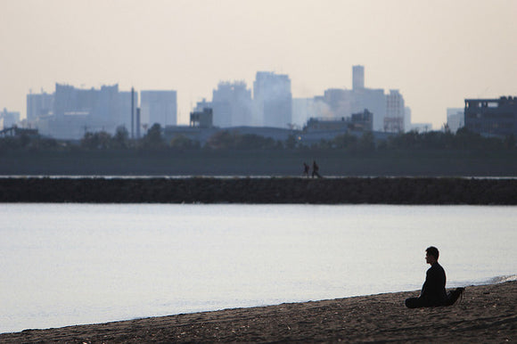 person sitting in meditation by water with a cityscape in the background
