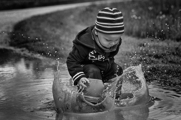 small child joyfully jumping into a mud puddle