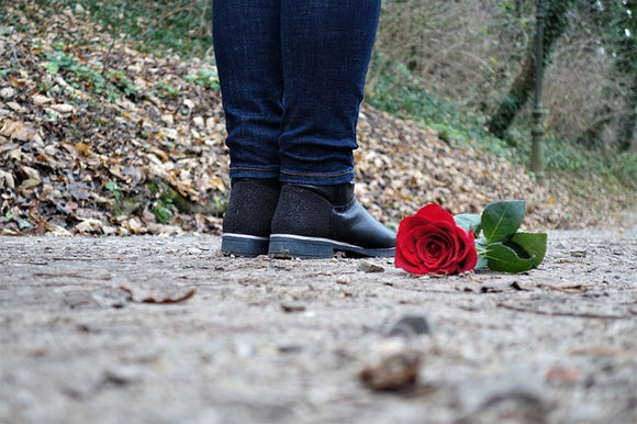 red rose on ground next to someone's feet