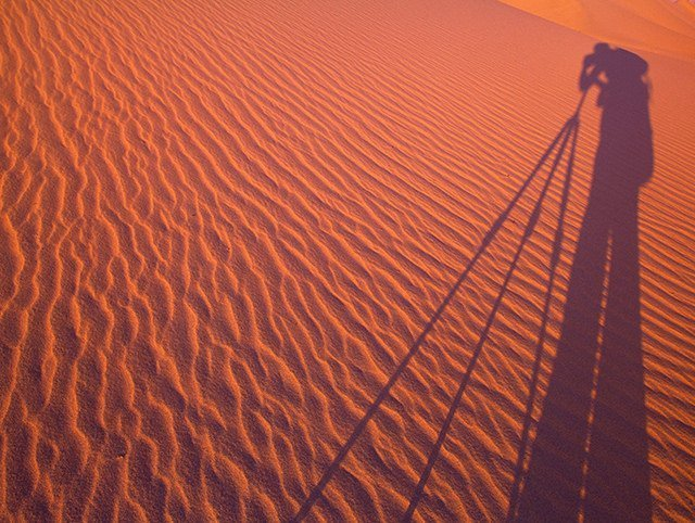 shadow on person standing behind camera tripod on sand