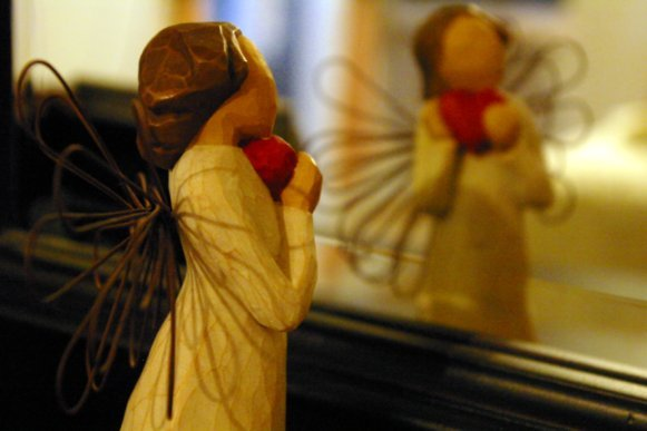 angle statue holding a heart and looking in mirror at herself