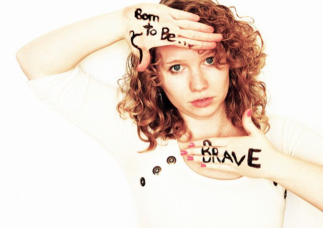 """Woman with the words """"Born to be ... Brave"""" written on her hands that she is holding by her face"""
