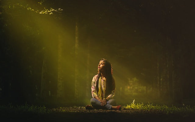 woman sitting on ground lit by a sunbeam in a dark forest setting