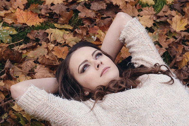 woman laying on ground in bed of fall leaves staring upward