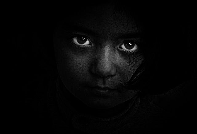 child's face peering out of the darkness