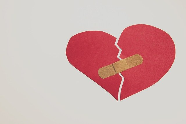 red construction paper broken heart with band aid over break