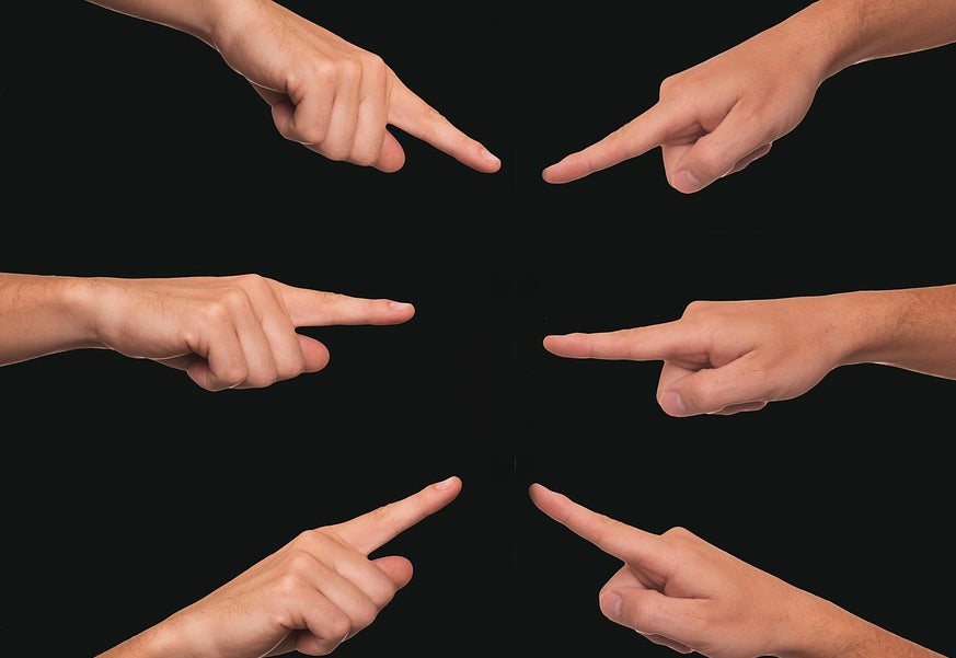 fingers pointing at one another against a black background