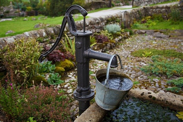 pump from well adding water to a bucket