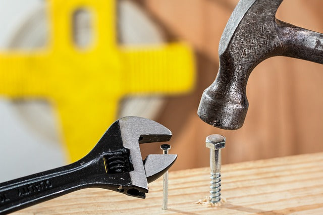 block of wood with a hammer driving a screw and a wrench screwing in a nail