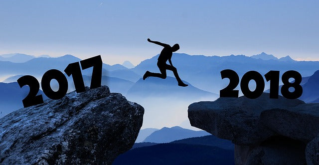silhouette of person leaping from one rock (labeled 2017) to another (labeled 2018)