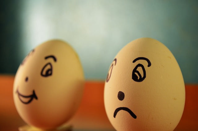 two eggs, one with a smiley face and one with a frown