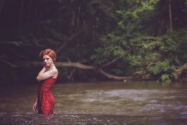 woman standing in a flowing river in a red dress