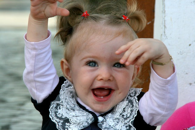 little girl with hands in the air and a joyful expression on her face