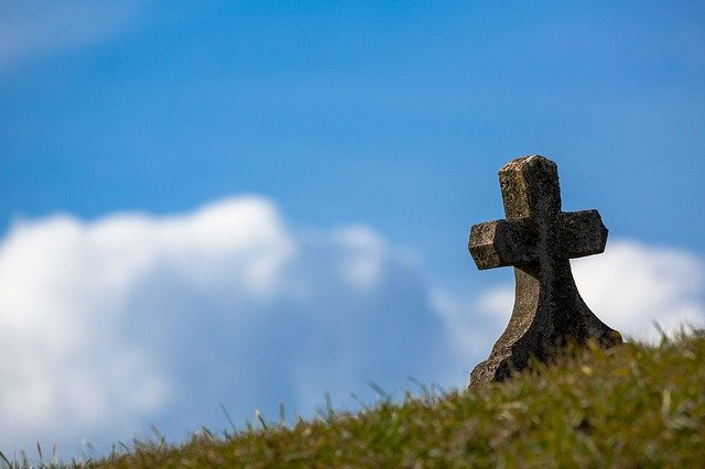 cross gravestone against blue sky background