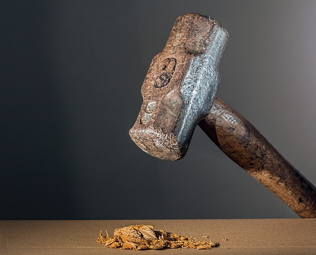 hammer raised above crushed peanut shell on table top