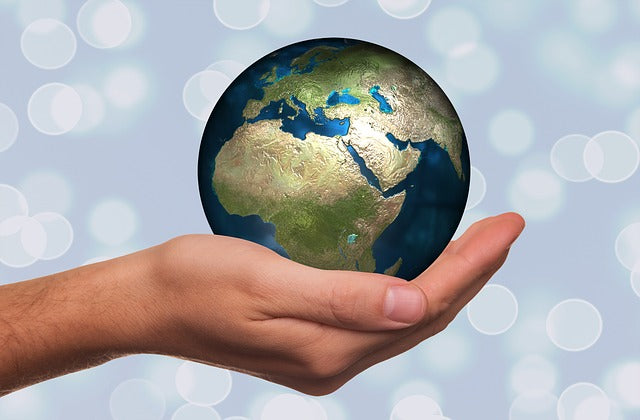 A small globe of the earth being held in the palm of someone's hand