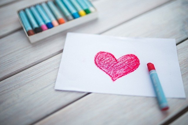 heart drawn on piece of paper with box of pastels nearby