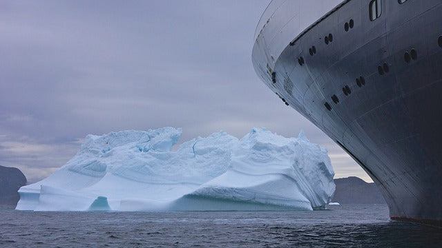 front edge of large boat with iceberg just ahead of it in ocean