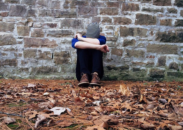 person sitting alone on ground against wall with head on knees and arms wrapped around head